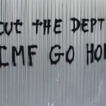 """A woman walks past a graffiti that reads """"Cut the debt, IMF go home"""" in Athens"""